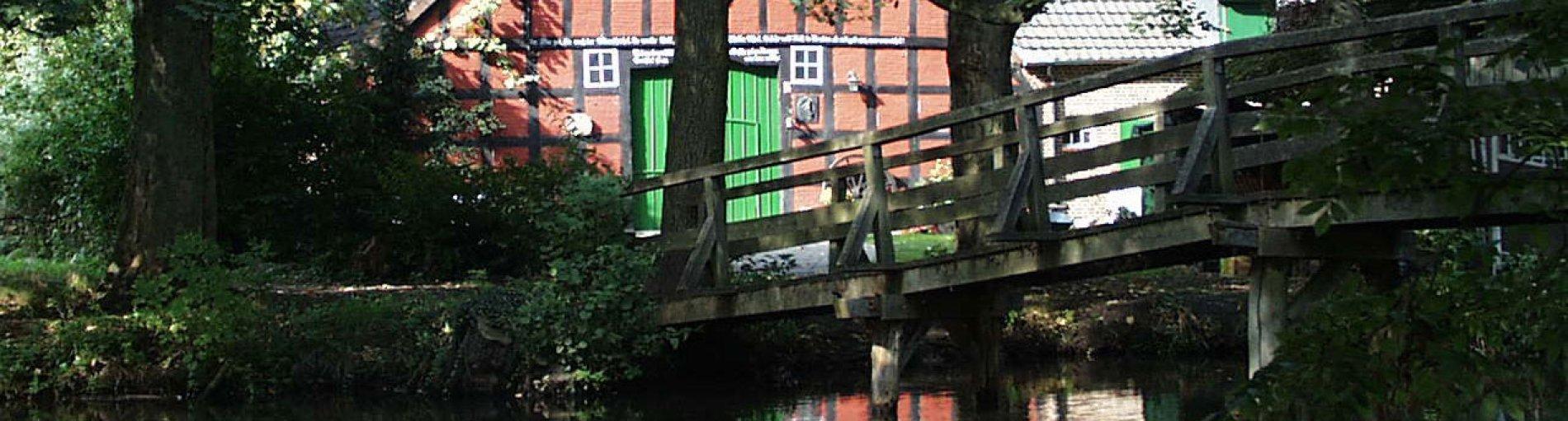 Eine hölzerne Brücke führt über einen Fluss zu einem Fachwerkhaus.
