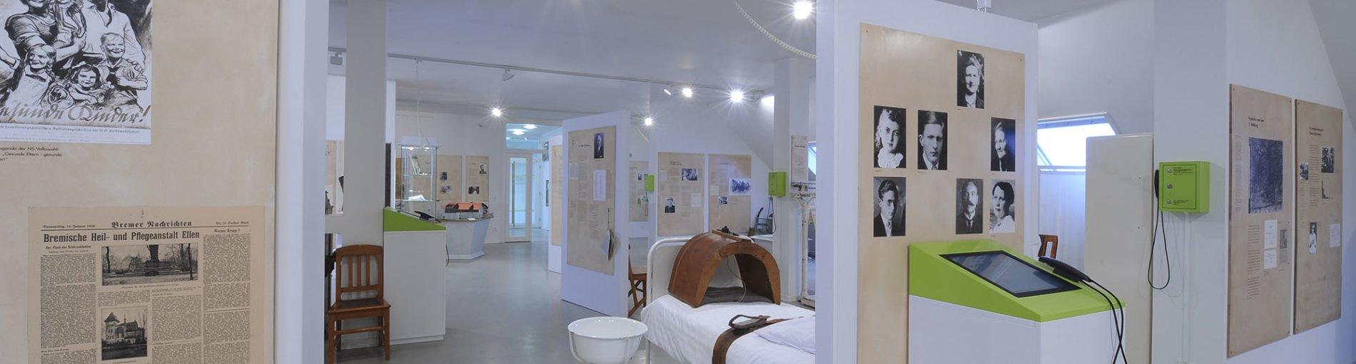 Eine Innenaufnahme aus dem hellen Krankenhausmuseum. Zu sehen sind einige Ausstellungsstücke sowie schwarz-weiß Bilder und Infotexte.