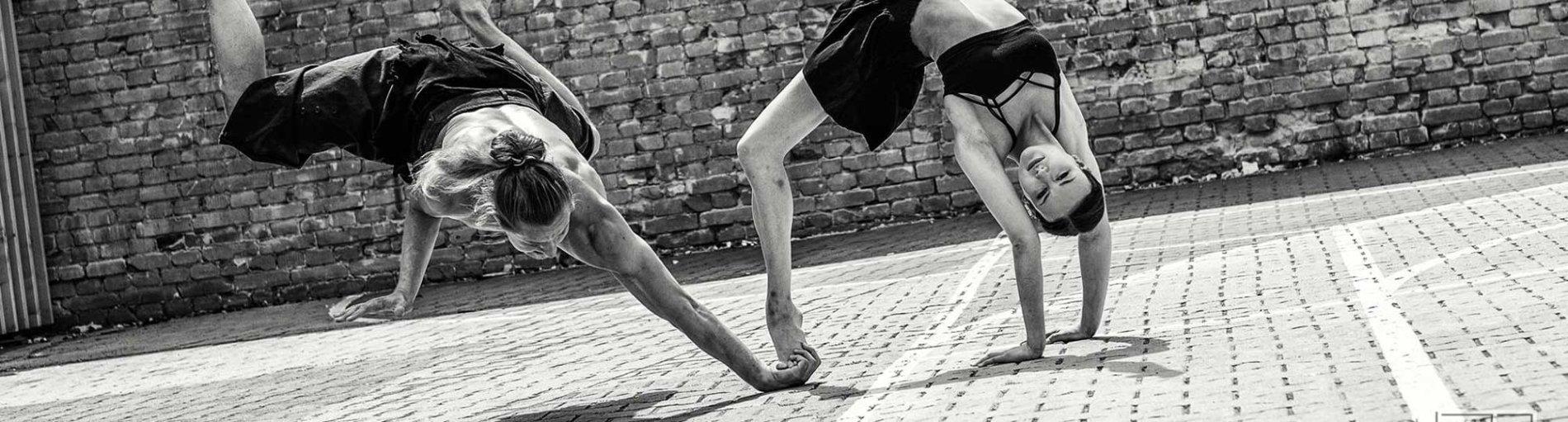 Ein Breakdancer und eine Ballerina am Tanzen. Bild in schwarz-weiß.