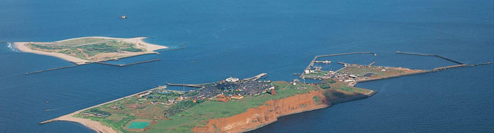 Eine Luftaufnahme der kompletten Insel und der Helgoland-Düne oben links im Bild. Quelle: Kurverwaltung Helgoland