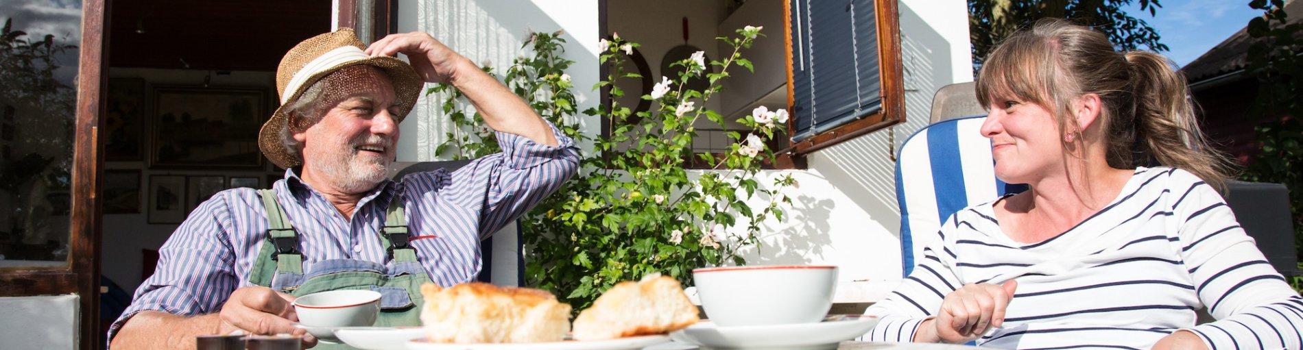 Ein Mann und eine Frau sitzen an einem Gartentisch und lachen sich zu; Quelle: WFB/Jens Lemkühler
