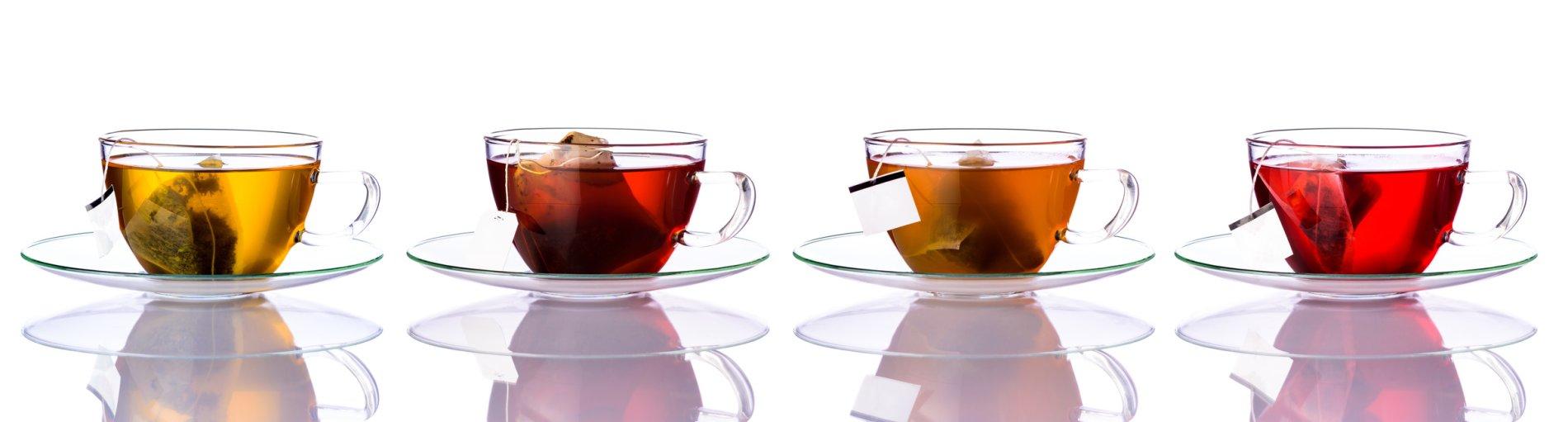 Vier Teegläser sind mit unterschiedlichen Teesorten gefüllt vor einem weißen Hintergrund.