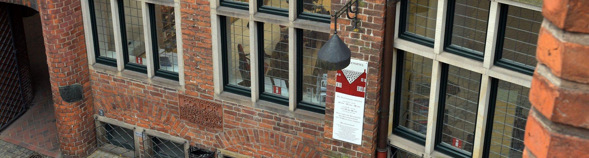 Der Blick von oben fällt auf die Wand eines Backsteingebäudes mit Fenstern. Hinter den Fenstern sind Büroräume zu erkennen. Links ist ein Durchgang in der Backsteinwand zu sehen.