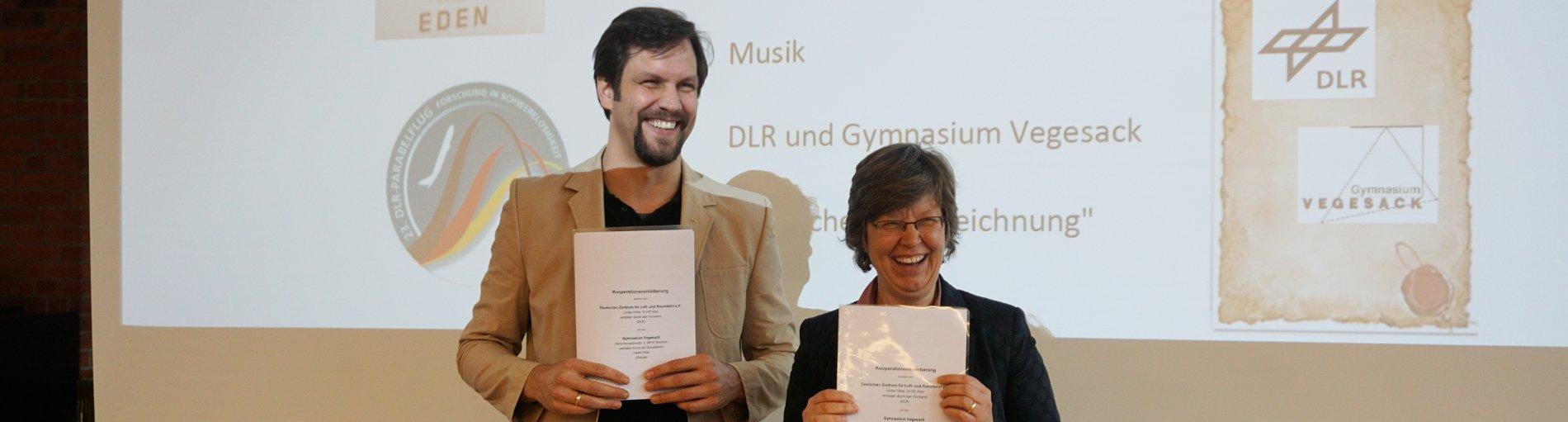 Ein Mann und eine Frau stehen vor einer Präsentationswand, vor sich ein Blatt Papier haltend und grinsen fröhlich.