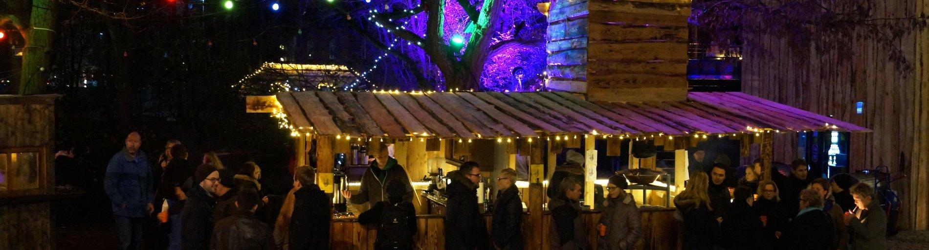 Eine Gruppe von Menschen steht an einer erleuchteten, aus Brettern gefertigten Bude an der Getränke ausgeschenkt werden. Ein Mann in der Bude bedient eine Kundin. Die anderen Menschen stehen in kleinen Gruppen zusammen und unterhalten sich.