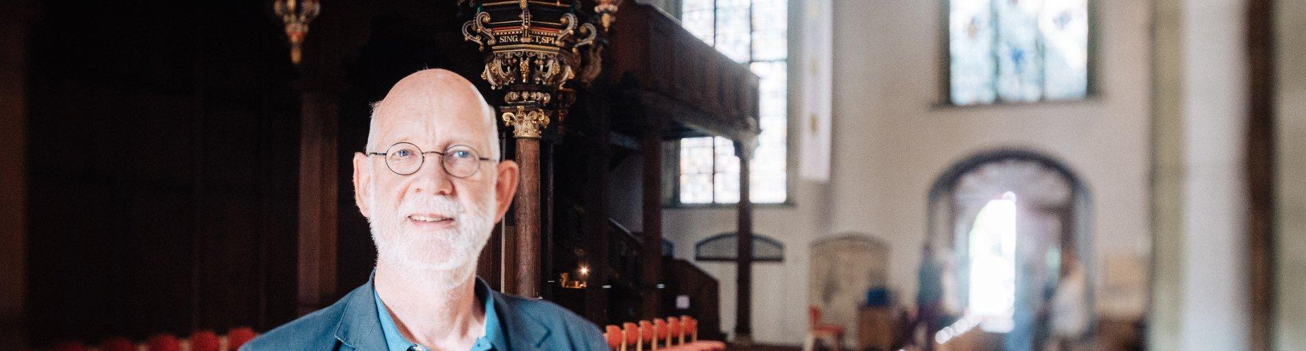 Ein älterer Herr mit Brille und blauen Sakko.