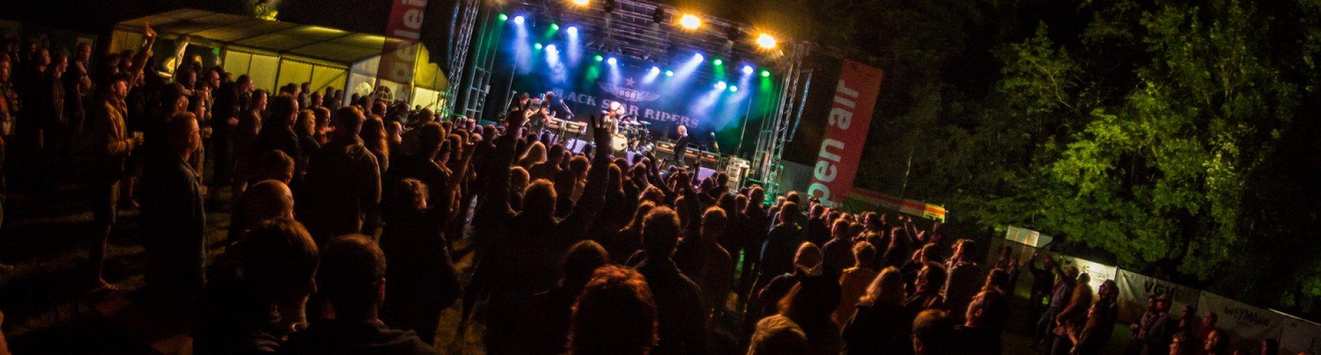 Das Ziegelei Open Air 2017 am späten Abend. Die Bühne ist bunt beleuchtet und davor feiert das Publikum.