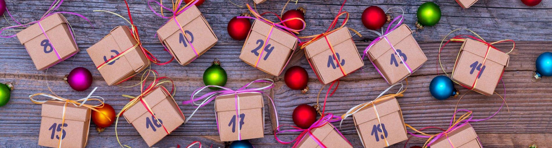 Viele kleine Päckchen mit Nummern für den Adventskalender sind auf einem Tisch verteilt.