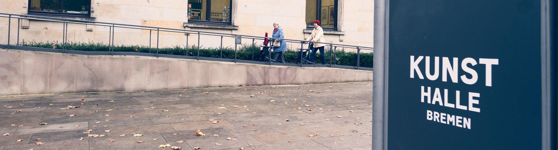 Zwei Damen mit Rollatoren laufen die Rampe vor der Kunsthalle Bremen herauf.