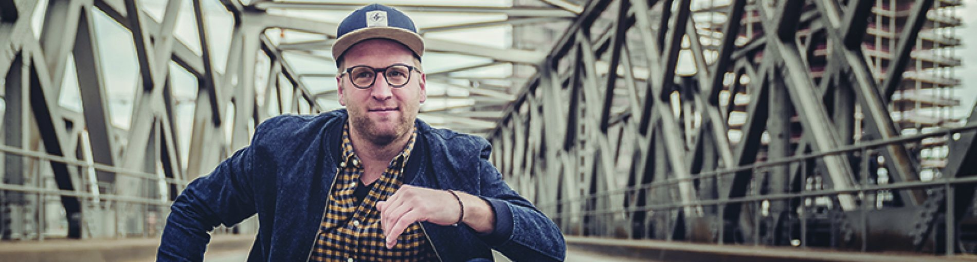 Das Foto zeigt den Comedian Benni Stark, wie er auf einer Fußgängerbrücke sitzt.