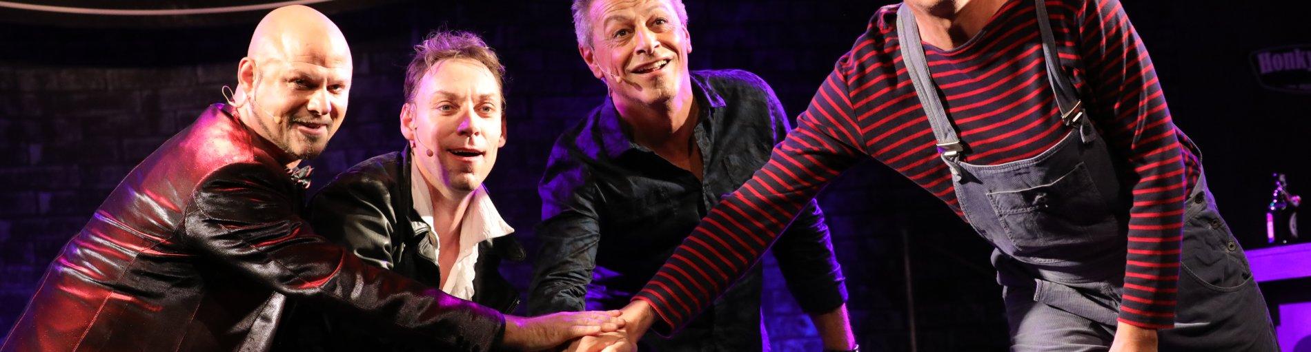 Vier Männer sind auf der Bühne und halten jeweils ihre Hand in die Mitte.