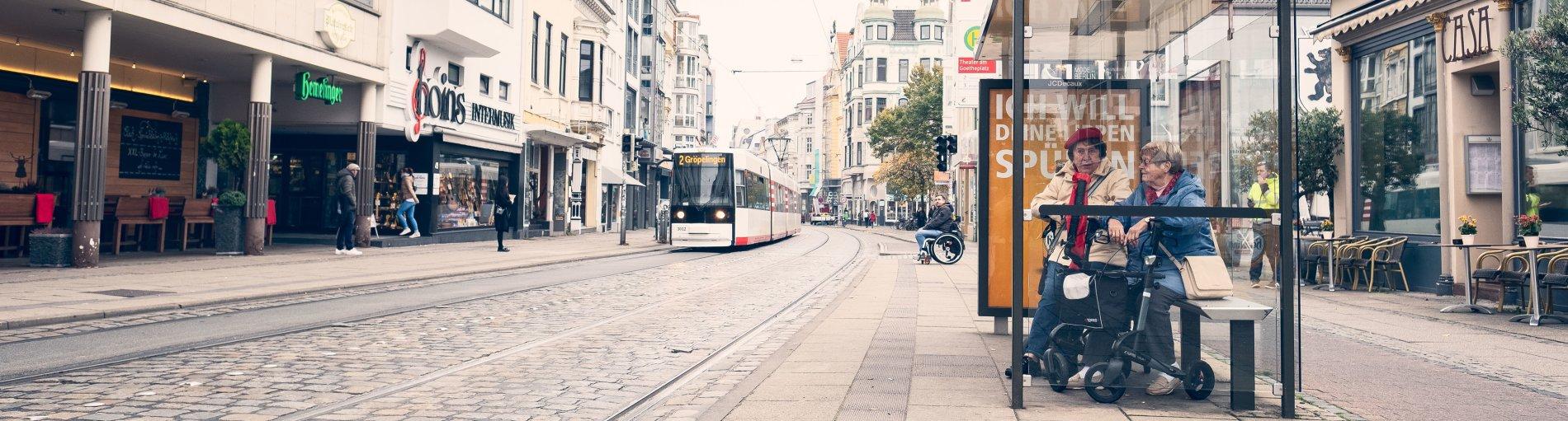 Zwei ältere Damen mit Rollator warten an einer Haltestelle. Eine Straßenbahn fährt vorbei. Im Hintergrund ist ein Mann im Rollstuhl zu sehen.