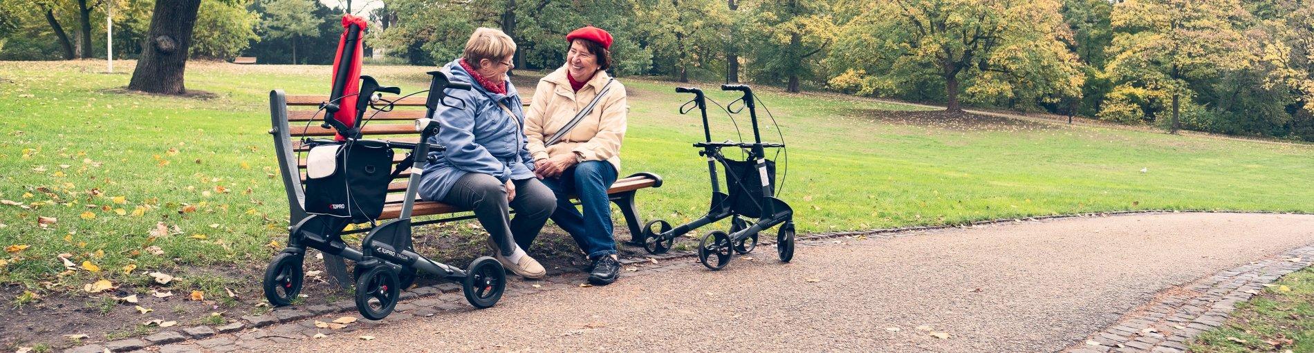 Zwei ältere Damen sitzen auf einer Parkbank und unterhalten sich fröhlich.