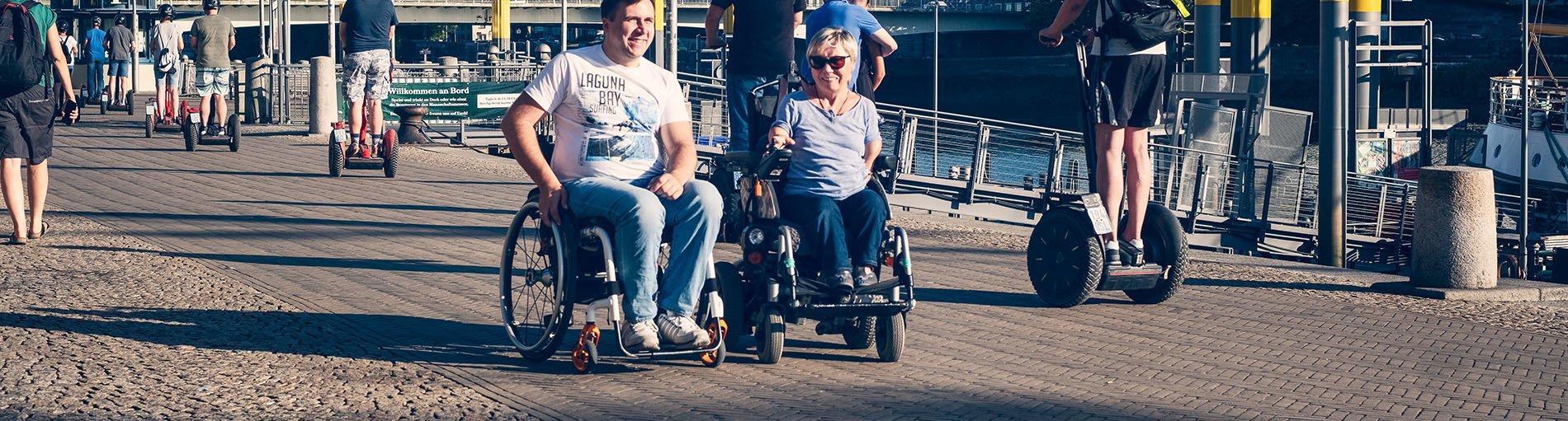 Ein lächelnder Mann und eine Frau im Rollstuhl an der Schlachte. Außerdem sind Menschen auf Segways unterwegs.