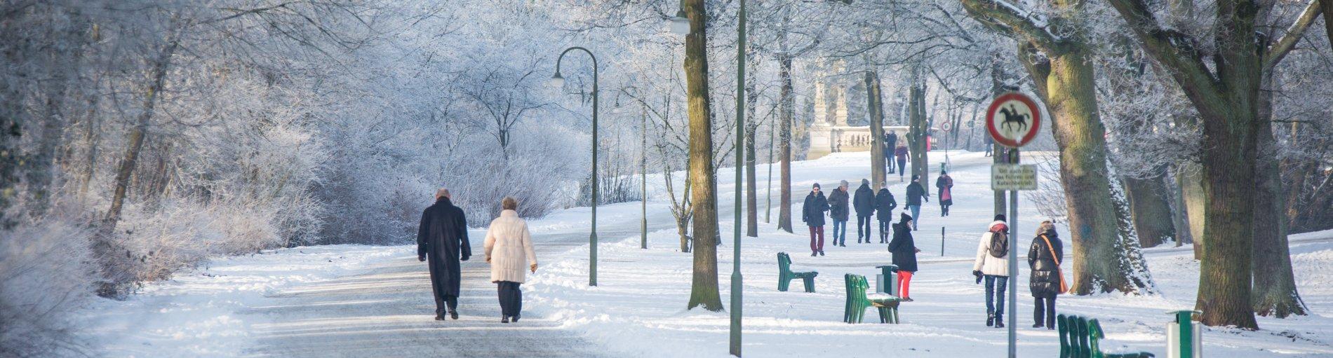 Menschen gehen bei Schnee im Bürgerpark spazieren