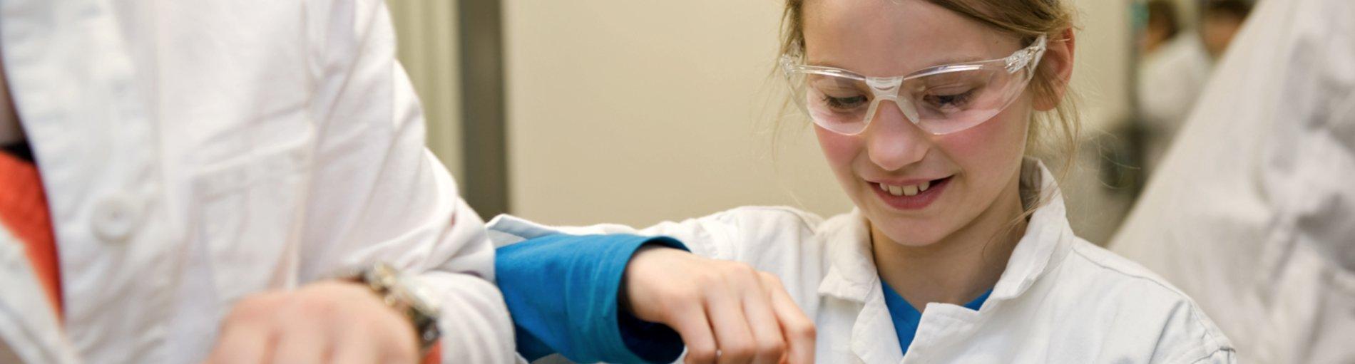 Mädchen in Kittel und Schutzbrille führt ein Experiment durch.