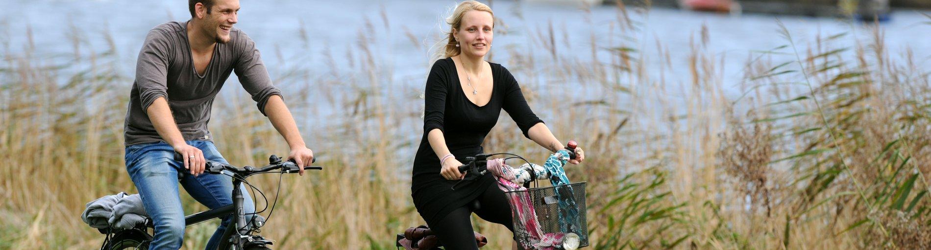 Zwei Menschen fahren Fahrrad am Wasser entlang.
