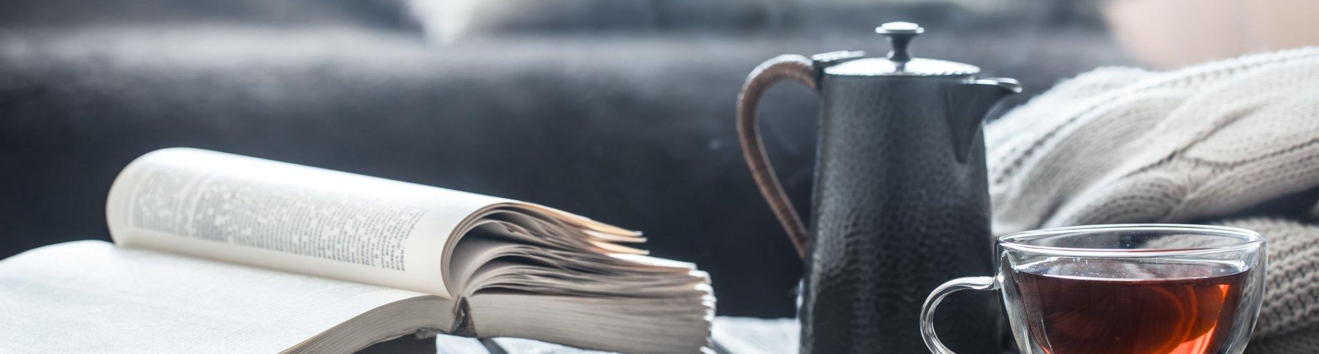 Ein aufgeschlagenes Buch liegt auf einem Holztisch, daneben steht eine Teekanne und ein gefülltes Teeglas. Im Hintergrund ein Sofa mit Kissen.