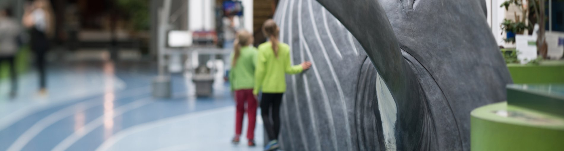 Im Vordergrund steht eine große Figur eines Buckelwal, im Hintergrund zwei Mädchen.