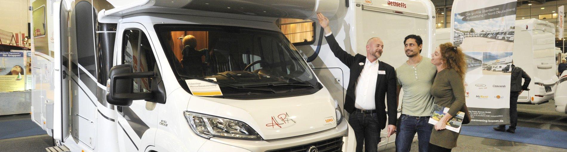Ein Aussteller präsentiert einem Pärchen einen Caravan
