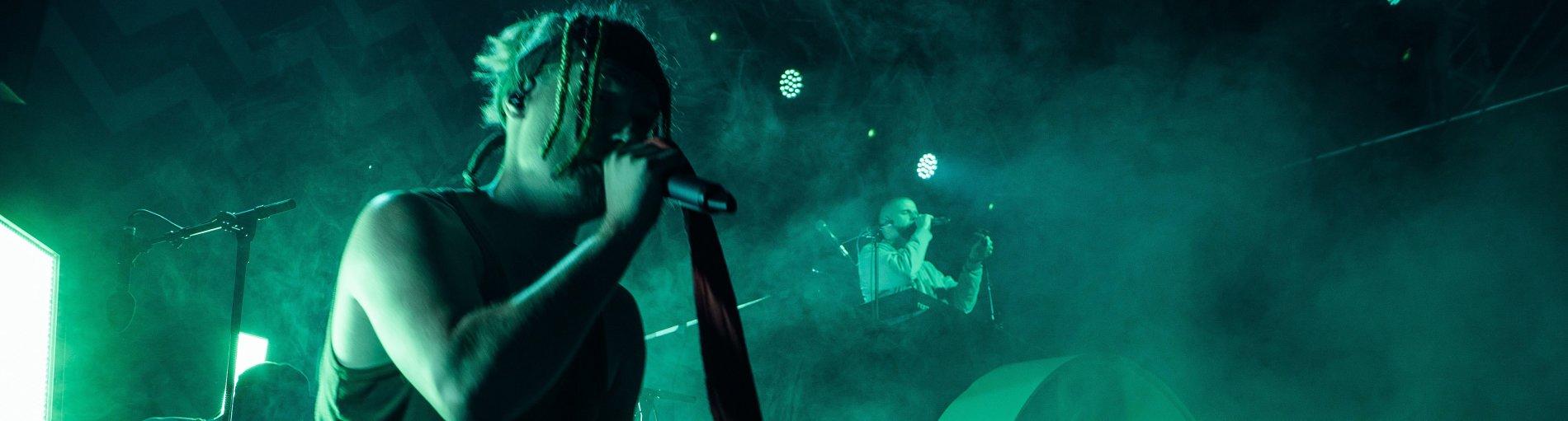 Die Orsons bei einem Auftritt. Der Liedsänger steht im Vordergrund und hat ein Mikrofon in der Hand.