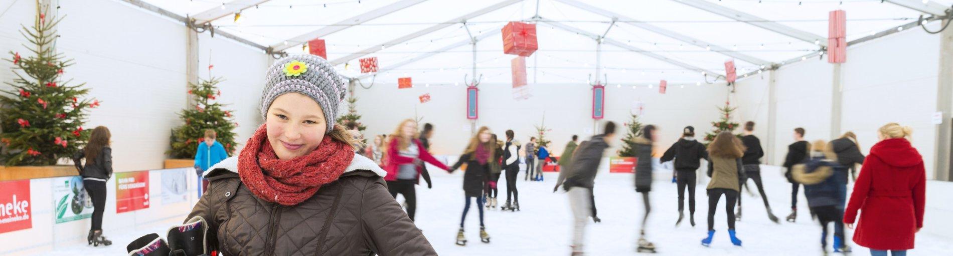 Ein Mädchen steht in Winterkleidung bekleidet in einer Eishalle, im Hintergrund laufen andere Kinder Schlittschuh