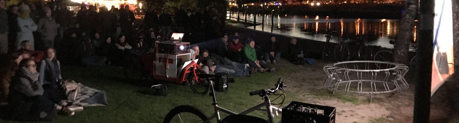 Eine Gruppe von Menschen sitzt am Weserstrand und schaut einen Film.