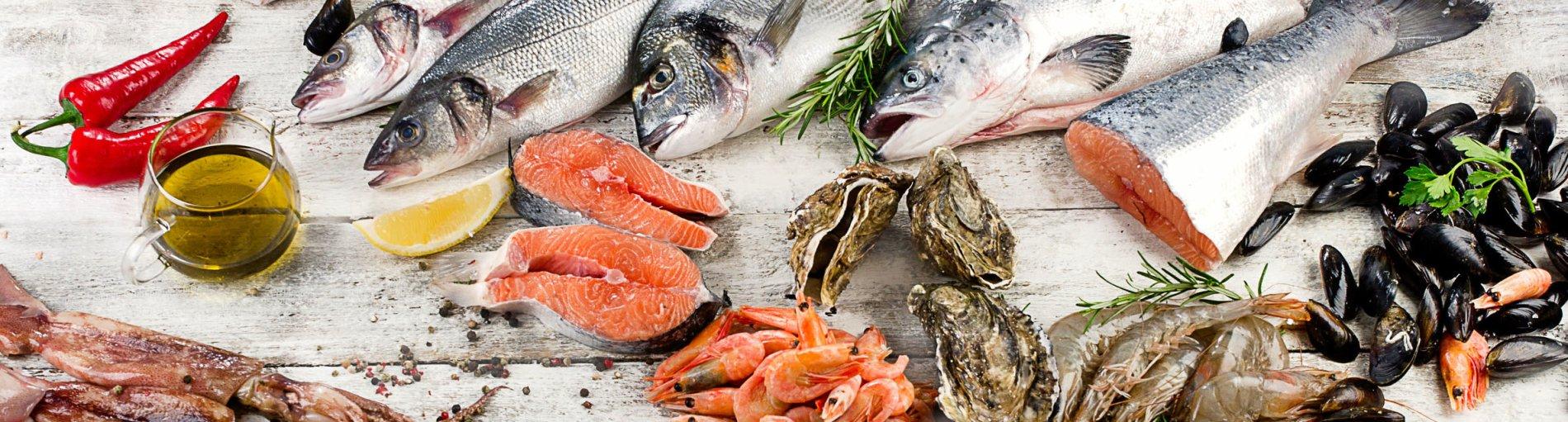 Verschiedene Fischsorten, Muscheln, Garnelen, Tintenfische und Lachs liegen auf einem Tisch.