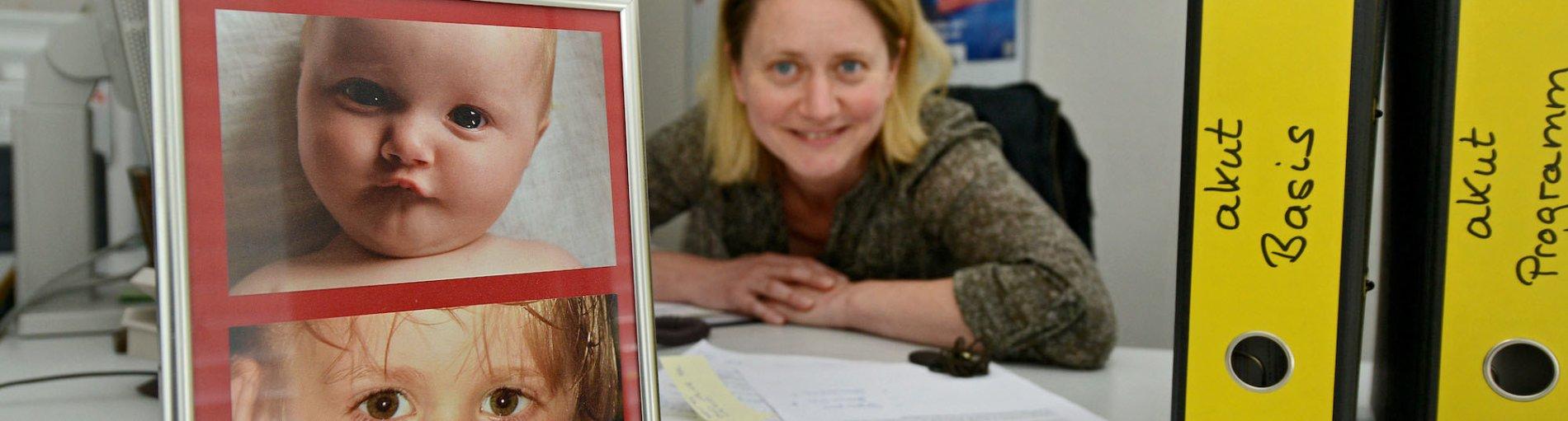 Eine Frau am Schreibtisch mit Kinderfotos.