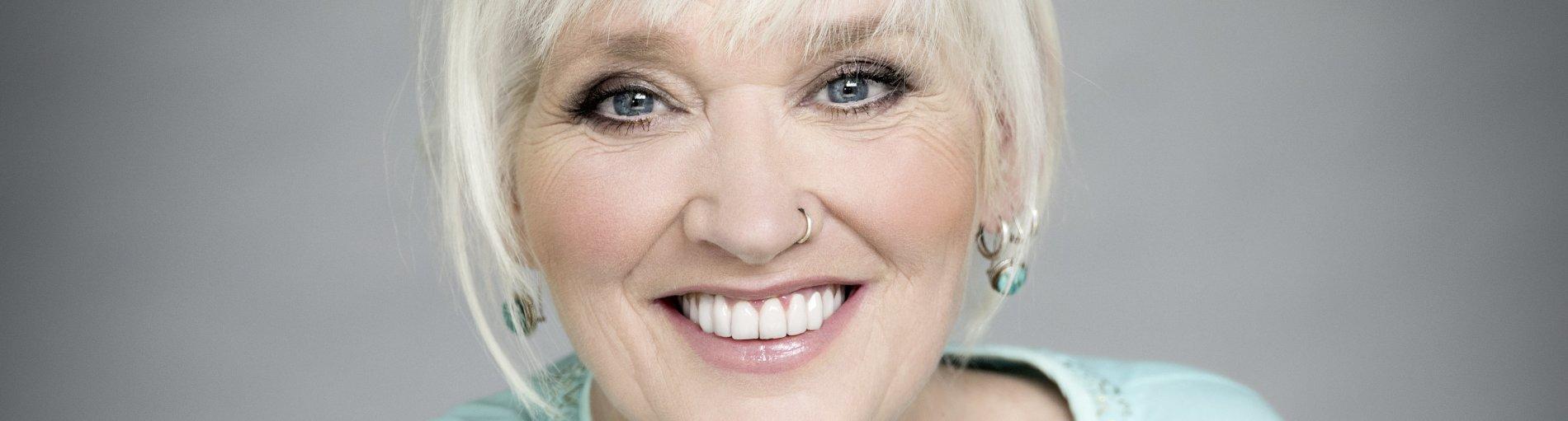 Comedian Gaby Köster blickt freundlich lächelnd in die Kamera.