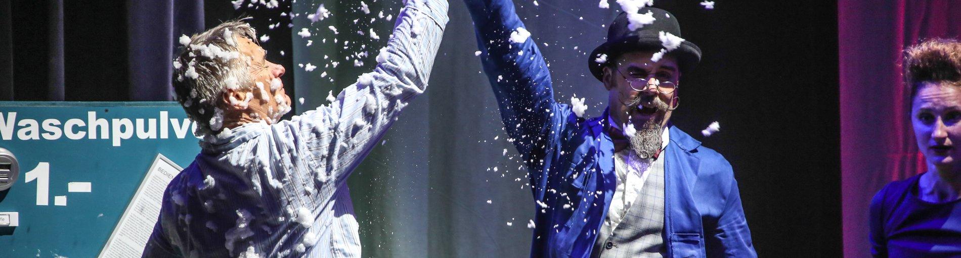 Zwei Schauspieler schlagen sich in die Hände mit Seifenschaum.