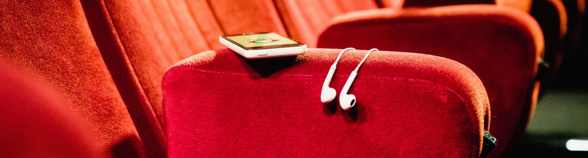 Rote Kinositze, auf einem Sitz liegt ein Smartphone mit Kopfhörern. Auf dem Smartphone ist die GRETA App geladen.