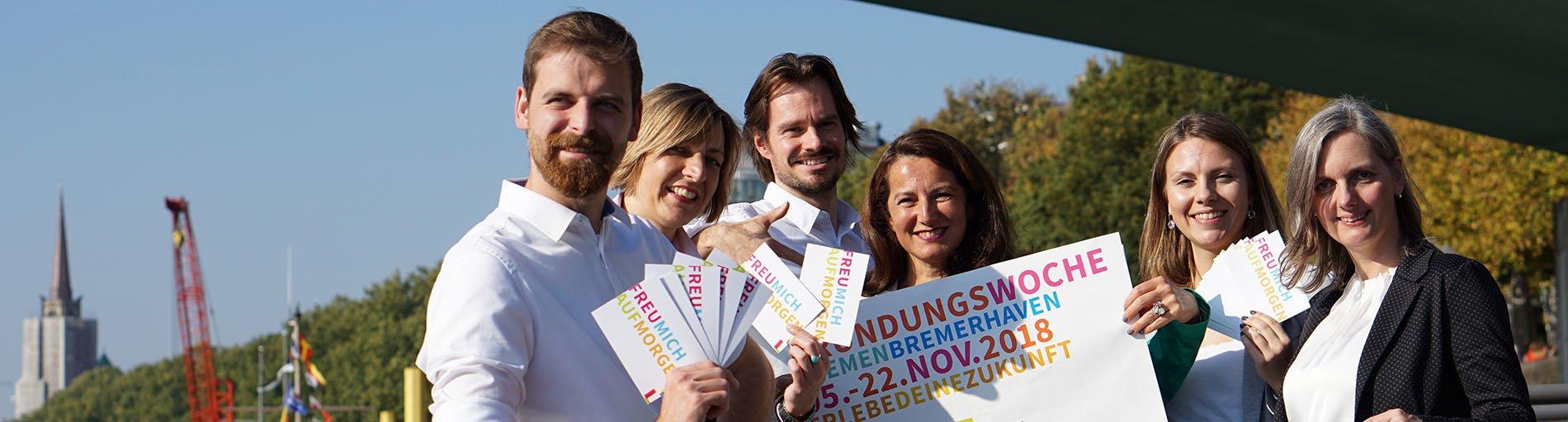 Sechs Personen halten Plakate und Flyer zur Gründungswoche 2018 in der Hand.