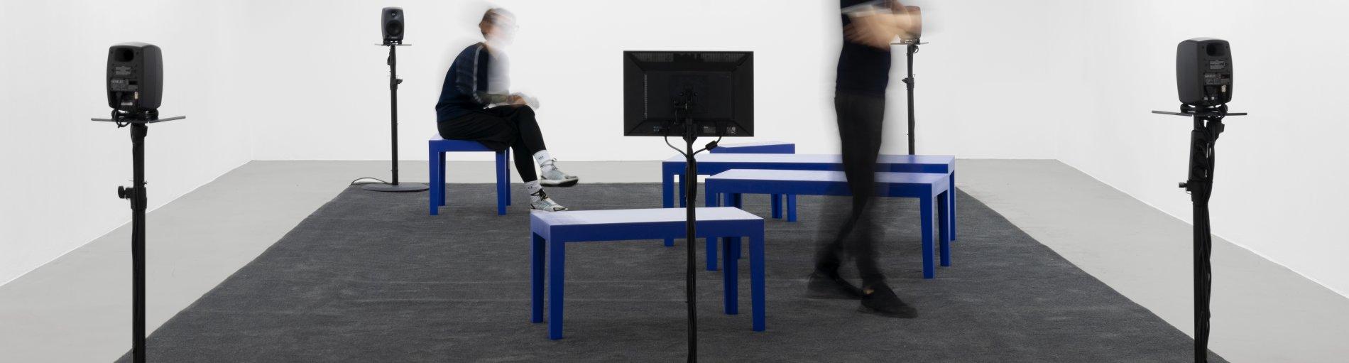 In einem weißen Raum stehen Lautsprecher und blaue Bänke.