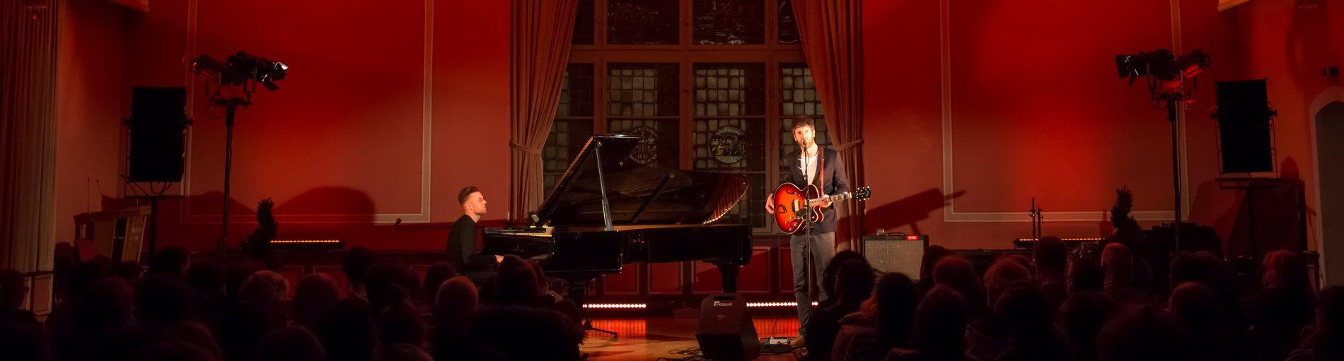 Ein Pianist und ein Gitarist in einem festlich beleuchteten Saal.