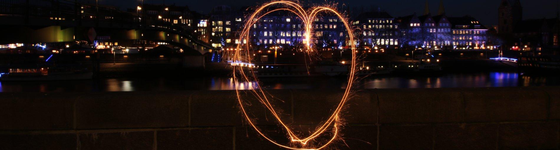 Ein leuchtendes Herz, das vor einer Steinmauer zu schweben scheint. Im Hintergrund ist die Weser und eine erleuchtete Häuserreihe zu sehen.