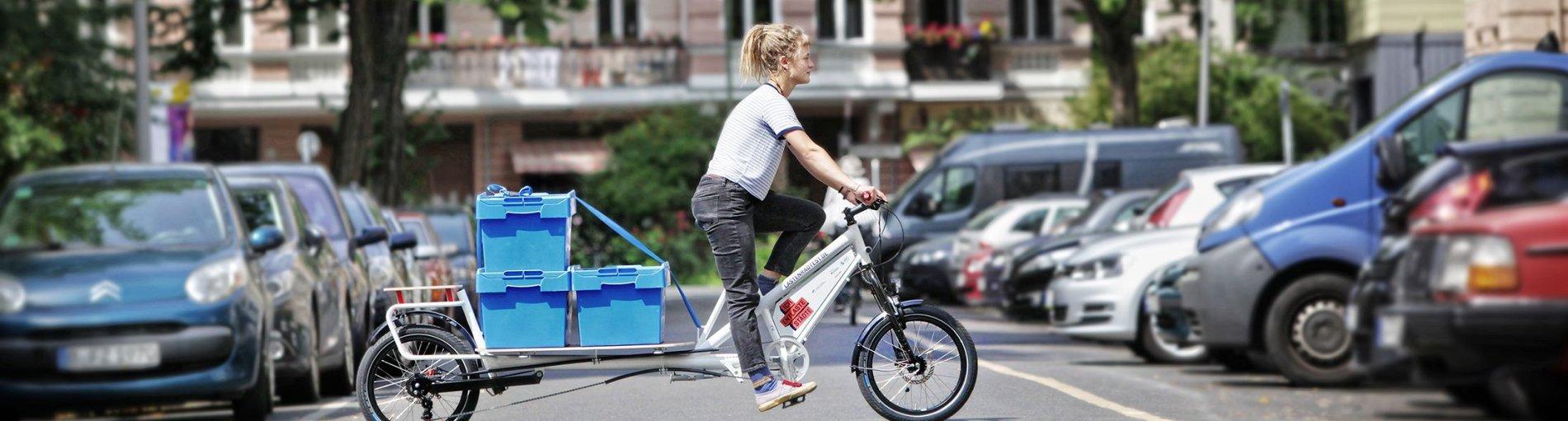 Eine Frau fährt auf einem Lastenfahrrad