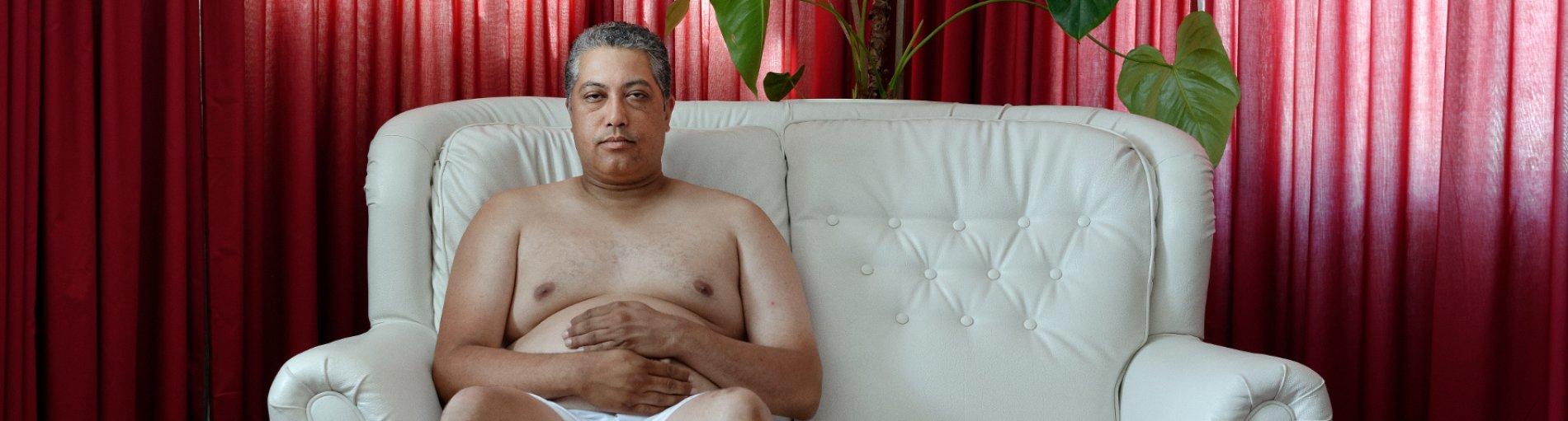 Ein Mann in Unterwäsche sitzt auf einem weißen Sofa