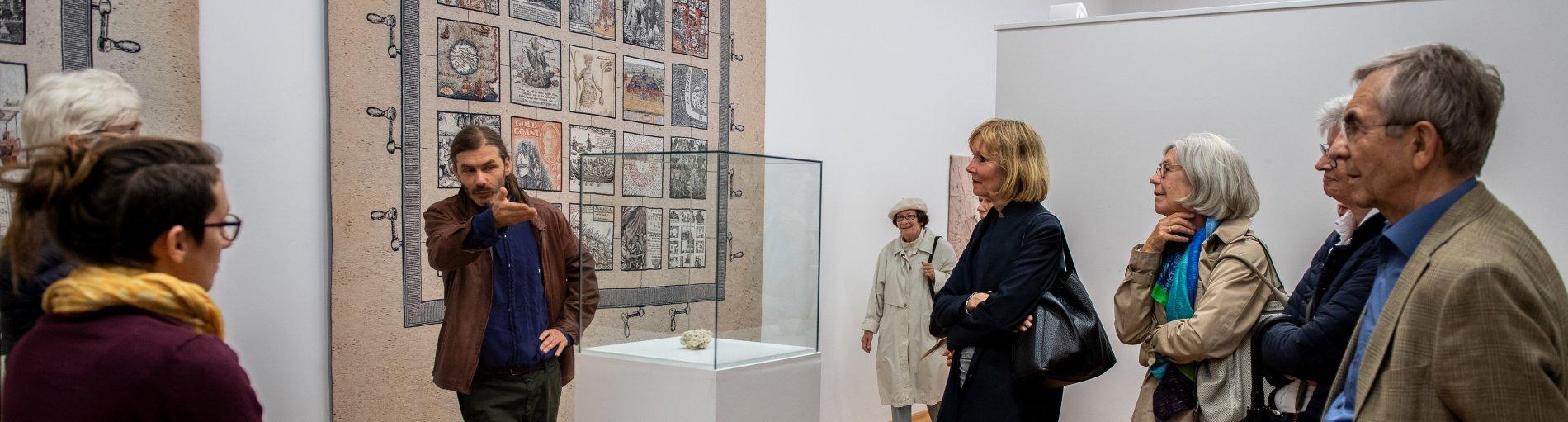 Der Künstler erläutert Besuchern im Haus im Schluh seine Arbeit.