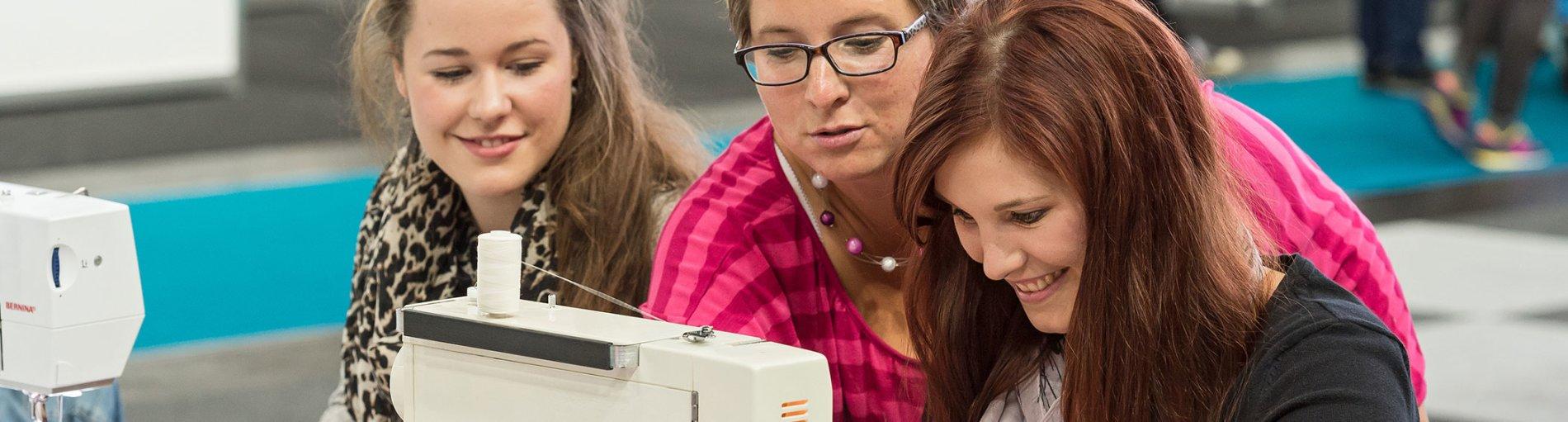 Eine Frau zeigt zwei anderen den Umgang mit der Nähmaschine.