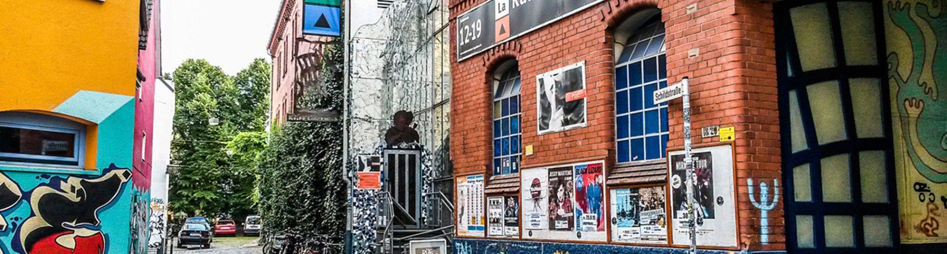 Backsteinfassade eines Hauses, bunt beklebt mit Plakaten.