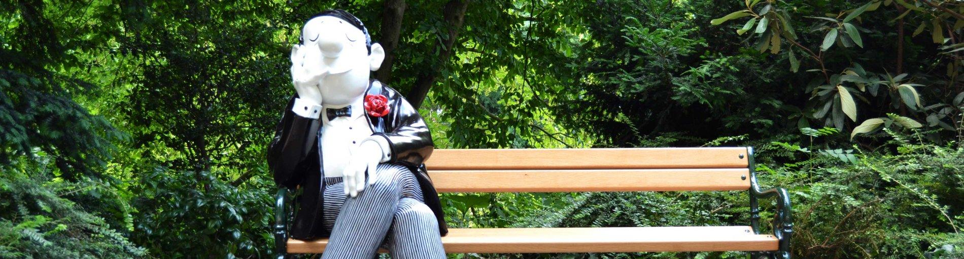 Eine Loriot-Figur sitzt auf einer Bank vor grün bewachsenen Bäumen