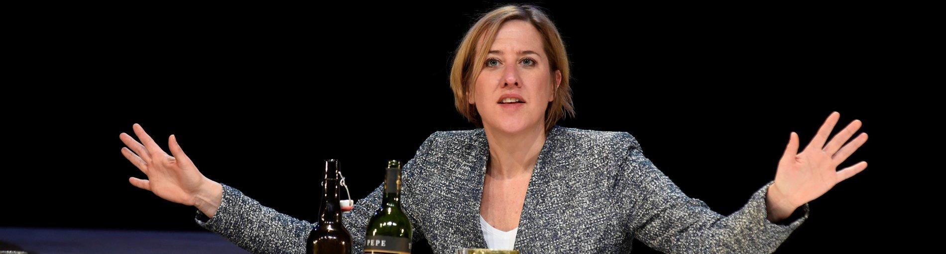 Eine Schauspielerin sitzt an einem Tisch mit einigen Weinflaschen und Trinkgläsern und hebt die Hände in die Luft.
