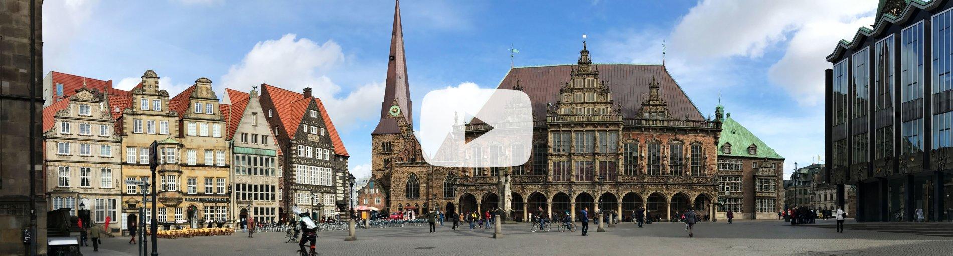 Eine Panoramaaufnahme des Bremer Marktplatzes. In der Mitte des Bildes befindet sich ein weißes, rechteckiges Logo.