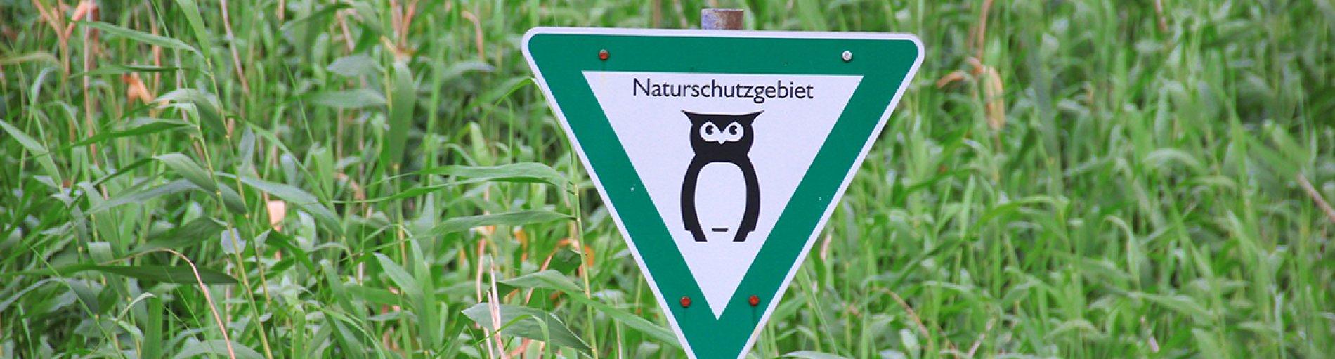 Hinweisschild weist Naturschutzgebiet aus.