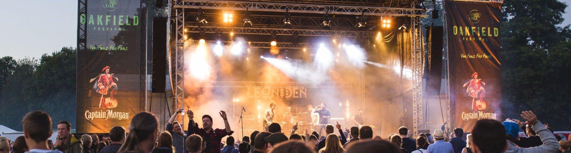 Musiker spielen auf einer Bühne, im Vordergrund Publikum