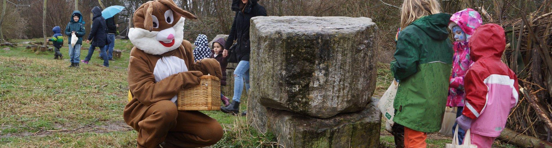 Ein Mann in einem Osterhasenkostüm unterstützt zwei Kinder bei der Suchaktion.
