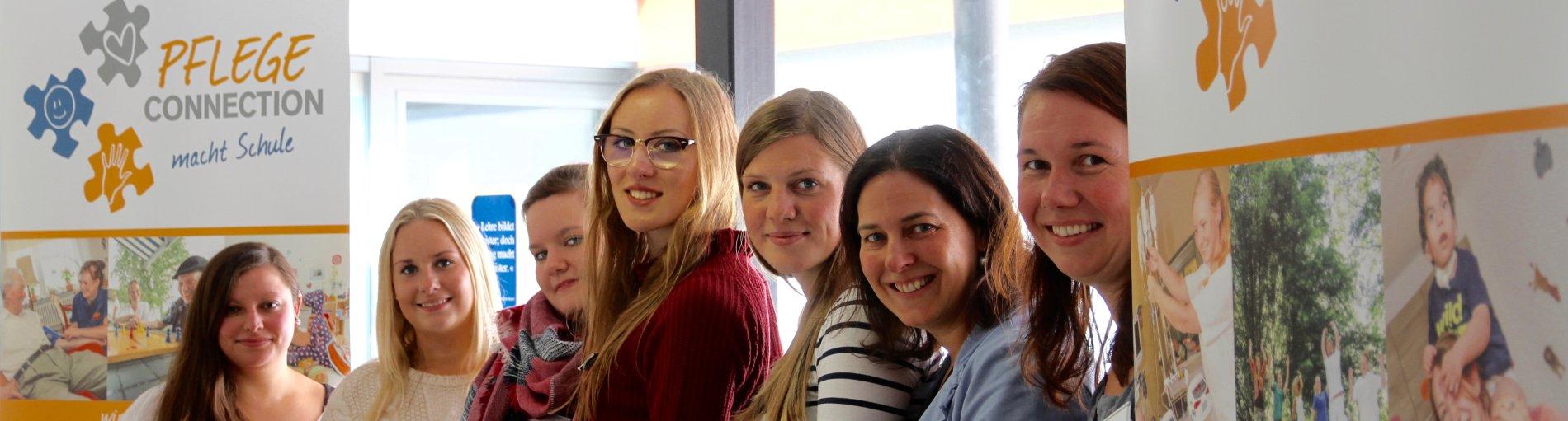 Ausbildung in der Pflege: Sieben junge Frauen blicken lächelnd in die Kamera.
