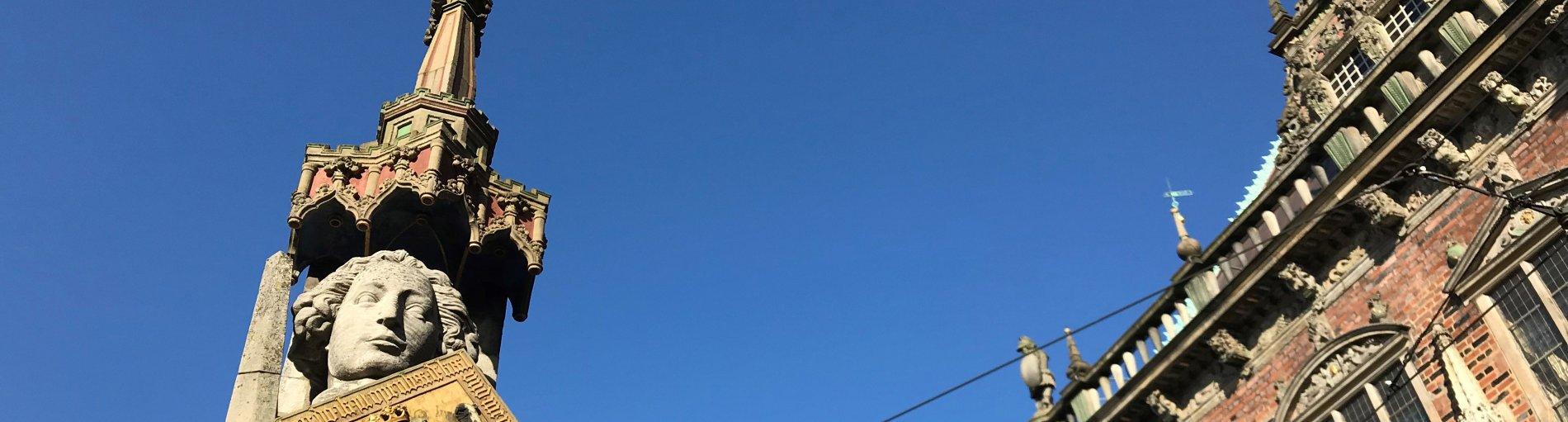 Der Kopf der Rolandstatue und eine Ecke des Rathausdaches bei blauem Himmel