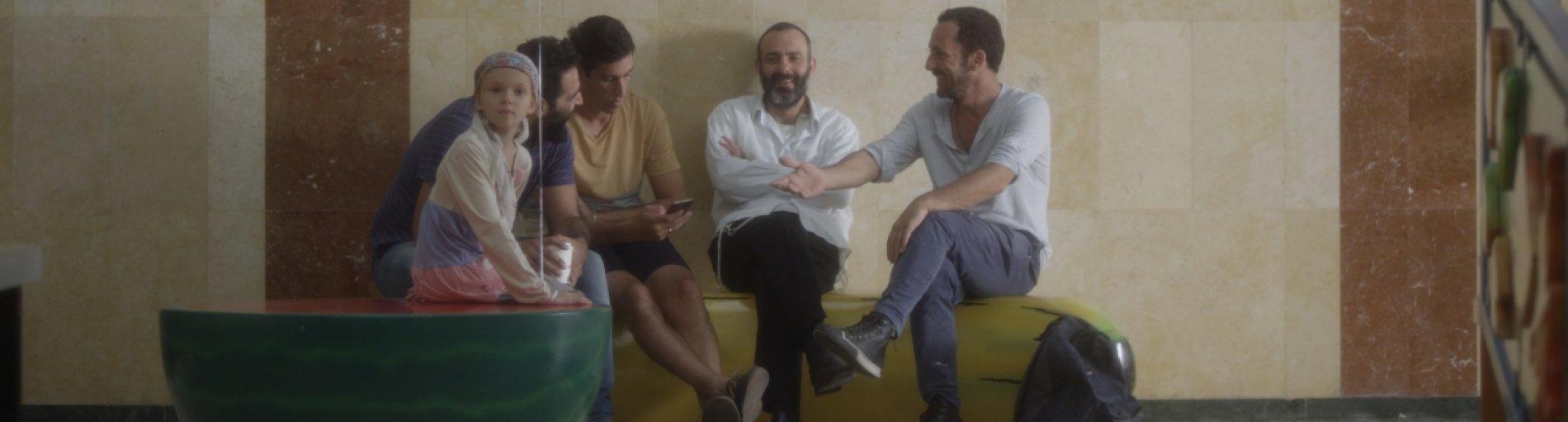 Vier Männer sitzen und unterhalten sich miteinander, während ein Mädchen neben ihnen sitzt mit einem hellblauen Luftballon in der Hand.